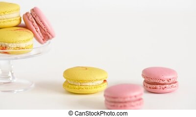 yellow and pink macarons on glass stand and table - sweets,...