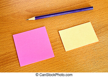 Yellow and pink memo with pencil on wood table