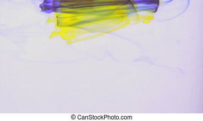 Yellow and purple ink swirling in w