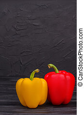Yellow and red bell peppers on dark background.