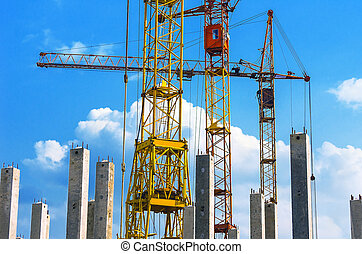 Yellow and Red Cranes, Vertical Reinforced Concrete Columns with Rebars against Blue Sky and White Clouds. Real Estate, Residential Buildings Urban Mixed-Use Development Concept.