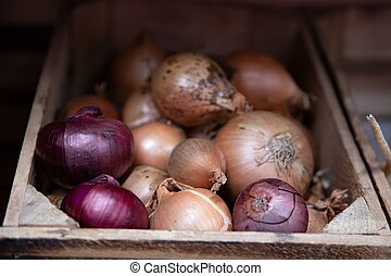 Yellow and red onions in a wooden case.