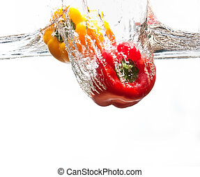 Yellow and red pepper falling into water