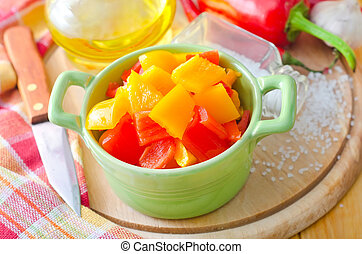 Yellow and red peppers on wooden background