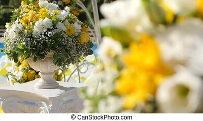 Yellow and white flowers in decorative vases to decorate yard for wedding ceremony