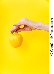 Yellow apple on a yellow background with hand. Zero waste and anti-plastic.