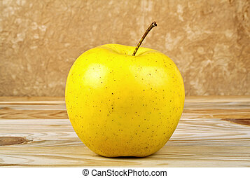 Yellow apple on wooden background