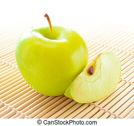 Yellow Apple with Apple Slice on the Bamboo Mat
