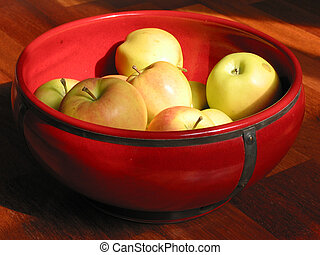 Yellow apples in a red bowl