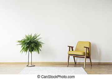 Yellow armchair against white wall