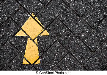 Yellow arrow paint on black brick concrete background