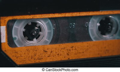 Yellow Audio Cassette in the Tape Recorder Playing and Rotates. Close-up. Vintage audio cassette tape with a blank label used for sound recording in a retro cassette player. Call recording. Macro