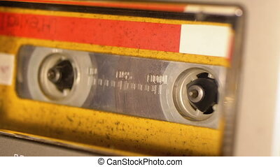 Yellow Audio Cassette in the Tape Recorder Playing and Rotates. Close up. Vintage audio cassette tape with a blank label used for sound recording in a retro cassette player. Call recording. Macro