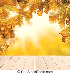 Yellow autumn background with white empty wooden table and fall oak leaves