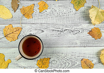 yellow autumn leaves, a Cup of tea on an old wooden background with empty space for text. the view from the top. flat lay