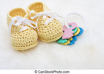 Yellow Baby Booties - Yellow baby booties with toy keys on a...