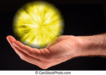 A hand holding a yellow ball of light against a black background.