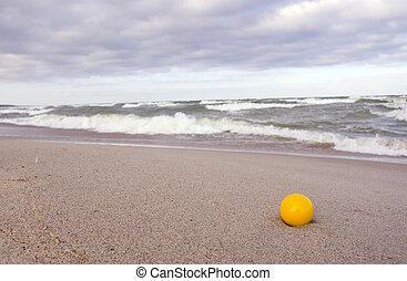 yellow ball on the sea beach sand