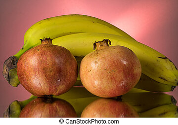 Yellow bananas and red pomegranate on mirroring table. Gorizontal image with copy space.