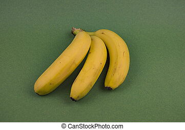 Yellow bananas on a green background laid out