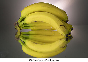 Yellow bananas on mirroring table. Gorizontal image with copy space.