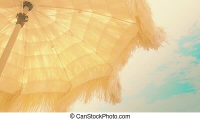 Yellow beach umbrella with waving fringe against the sky -...