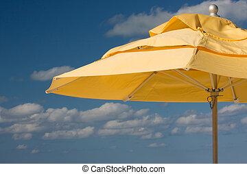 yellow sun umbrella against blue sky background