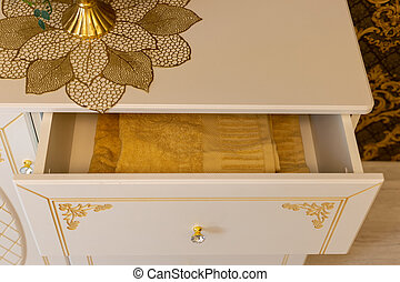 Yellow beautiful towel in a chest of drawers with gold inserts.