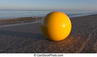 yellow billiards ball on sea beach