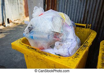 yellow bin full of rubbish in sidewalk in Thailand