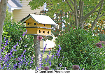 Yellow bird house surrounded by garden flowers