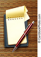 Yellow blank notepad with red pen