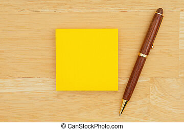 Yellow blank sticky note with a pen on textured wood background