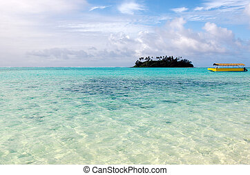 Yellow boat and mall coral islet at Muri Lagoon in Rarotonga Cook Islands.