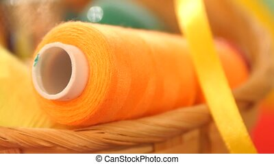 Yellow bobbin of thread with ribbon in the basket, close up...