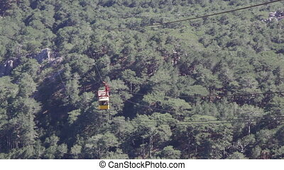 yellow booth of a ropeway on Ai Petri rises uphill over...