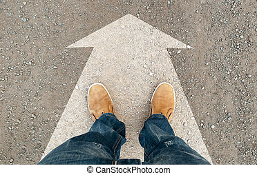 yellow boots on the road. a man standing on the road. the...