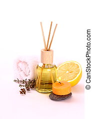 Yellow bottle with essential oil, candle and bath towel