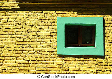 Yellow brick wall background with green window
