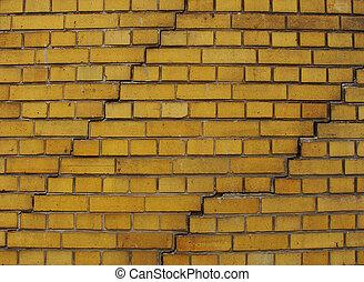 yellow brick wall with 2 large cracks