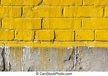 Yellow brick wall with paint stains