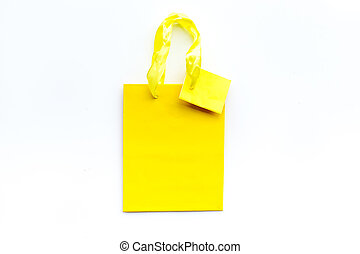 Yellow bright shopping bag on white background top view copyspace