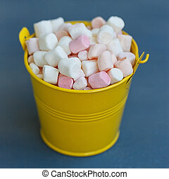 Yellow bucket with a marshmallow on blue wooden background