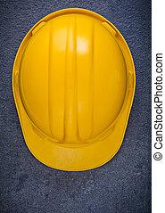 Yellow building helmet on black background construction concept