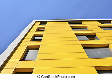 Yellow building with windows and blue sky