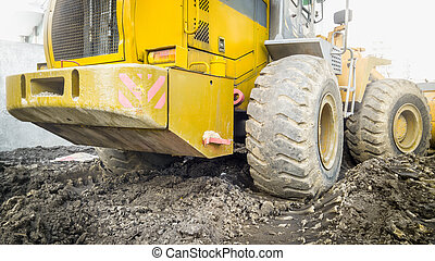 Yellow bulldozer covered in dirt working on ground