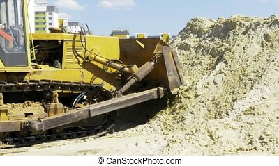 Yellow bulldozer in motion. Construction of a residential multi-apartment complex in the city. Construction. Stock video footage.