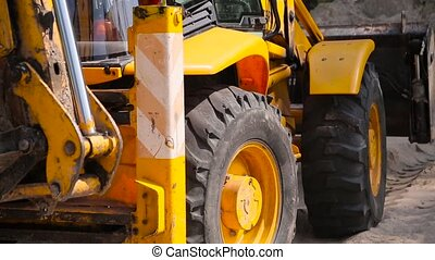 Yellow bulldozer scoop picks up