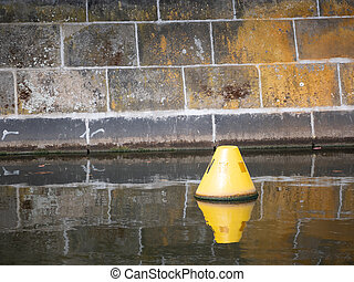 Yellow Buoy Floating In A Canal In Berlin, Germany