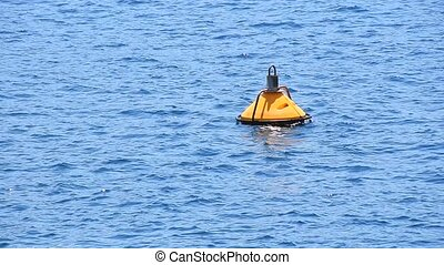 Yellow buoy floating in blue sea waves and ripples - Close...